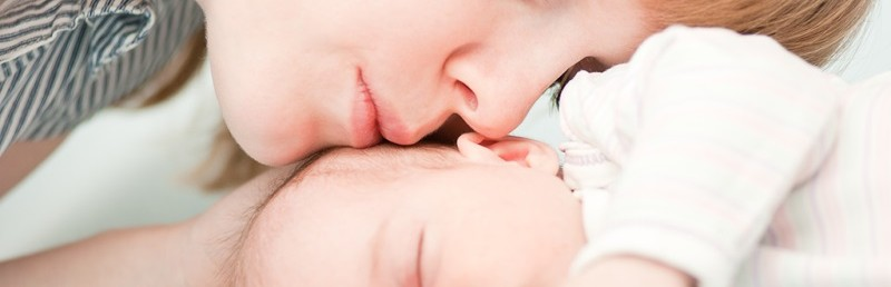 young mother kissing her slipping newborn baby
